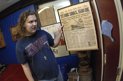 Christopher holds up a framed copy from the Boston Daily Globe